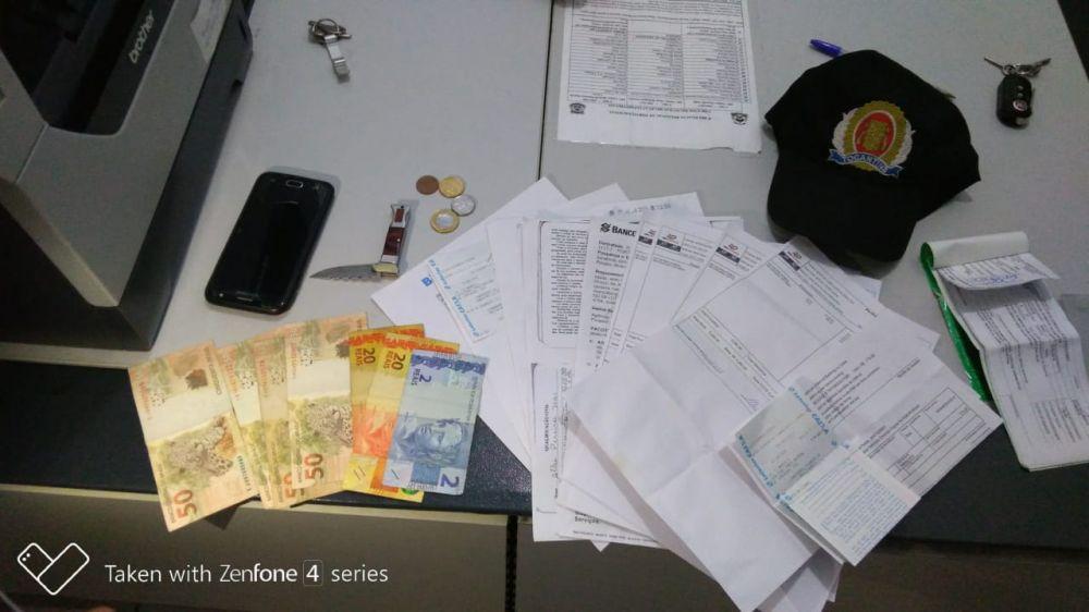 Documentos, comprovantes falsos e materiais apreendidos com o estelionatário – Foto: Divulgação/PMTO